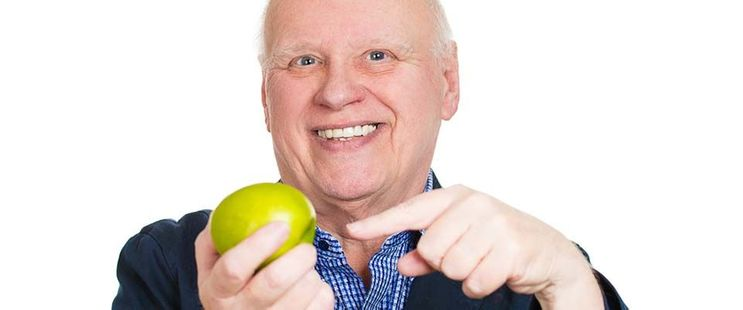 man pointing to a fruit in his hand